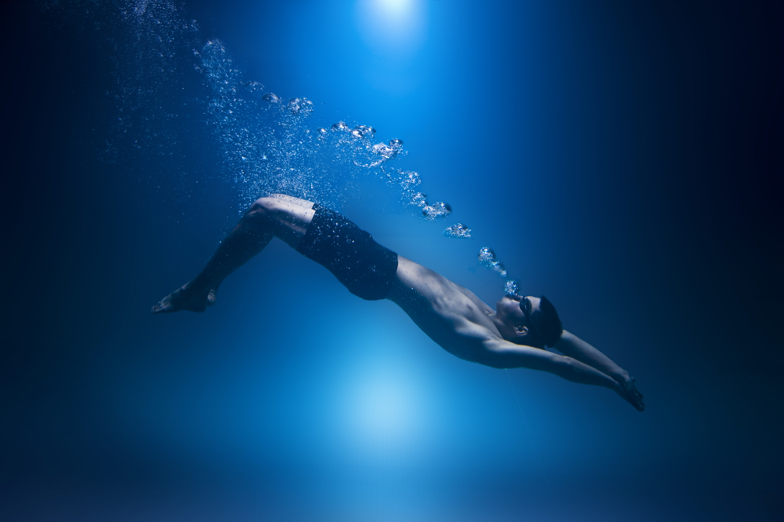 Swimmer underwater isolted exhaling bubbles blue background