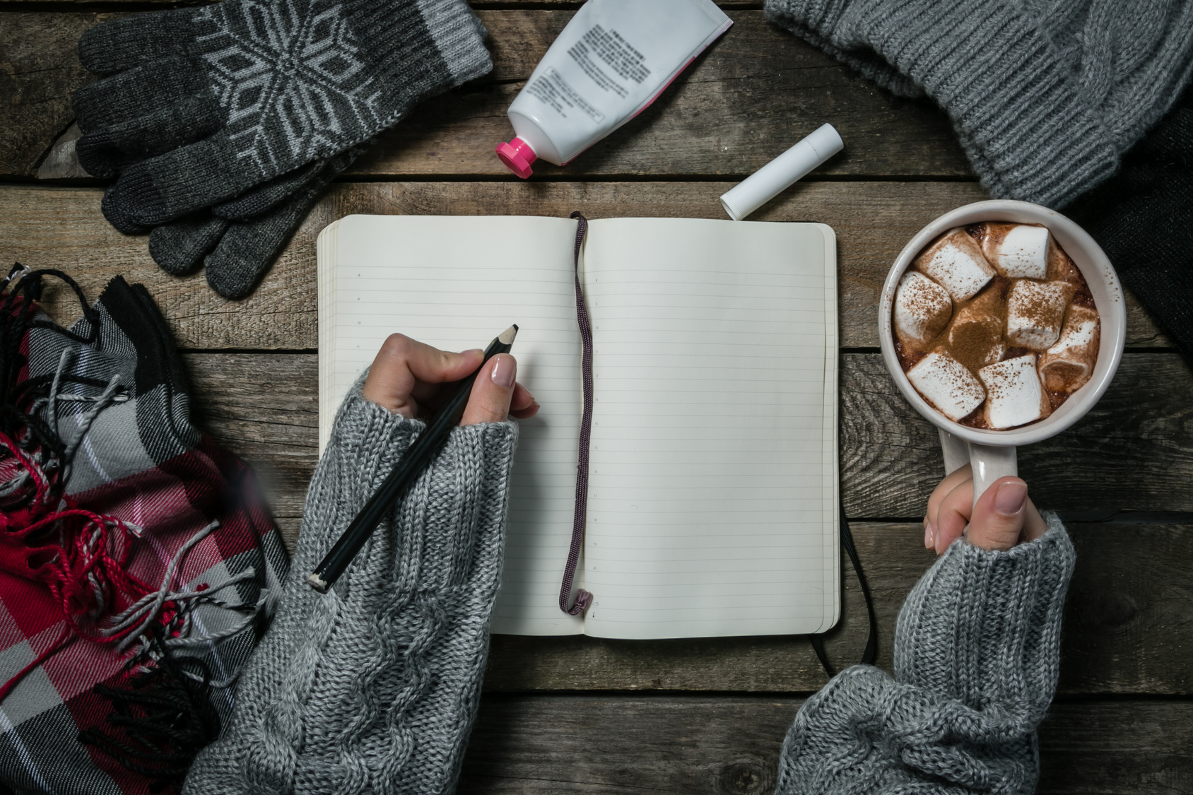 Winter weather survival kit concept. Female hands writing in notebook